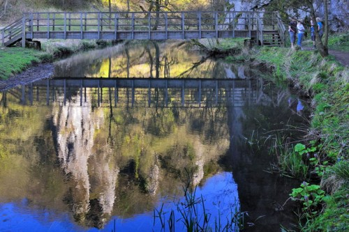 PIckering Tor and footbridge reflected in the calm waters of the River Dove