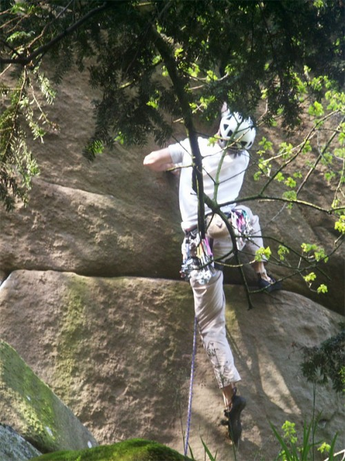 Rock climber above the Hermits Cave on Cratcliff Tor