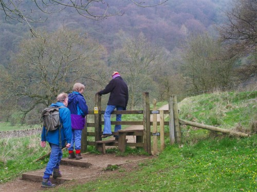 Walkers crossing a stile from White Lodge into Deep Dale